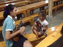 Zoe learning the ukulele with Pom at the Bamboo School